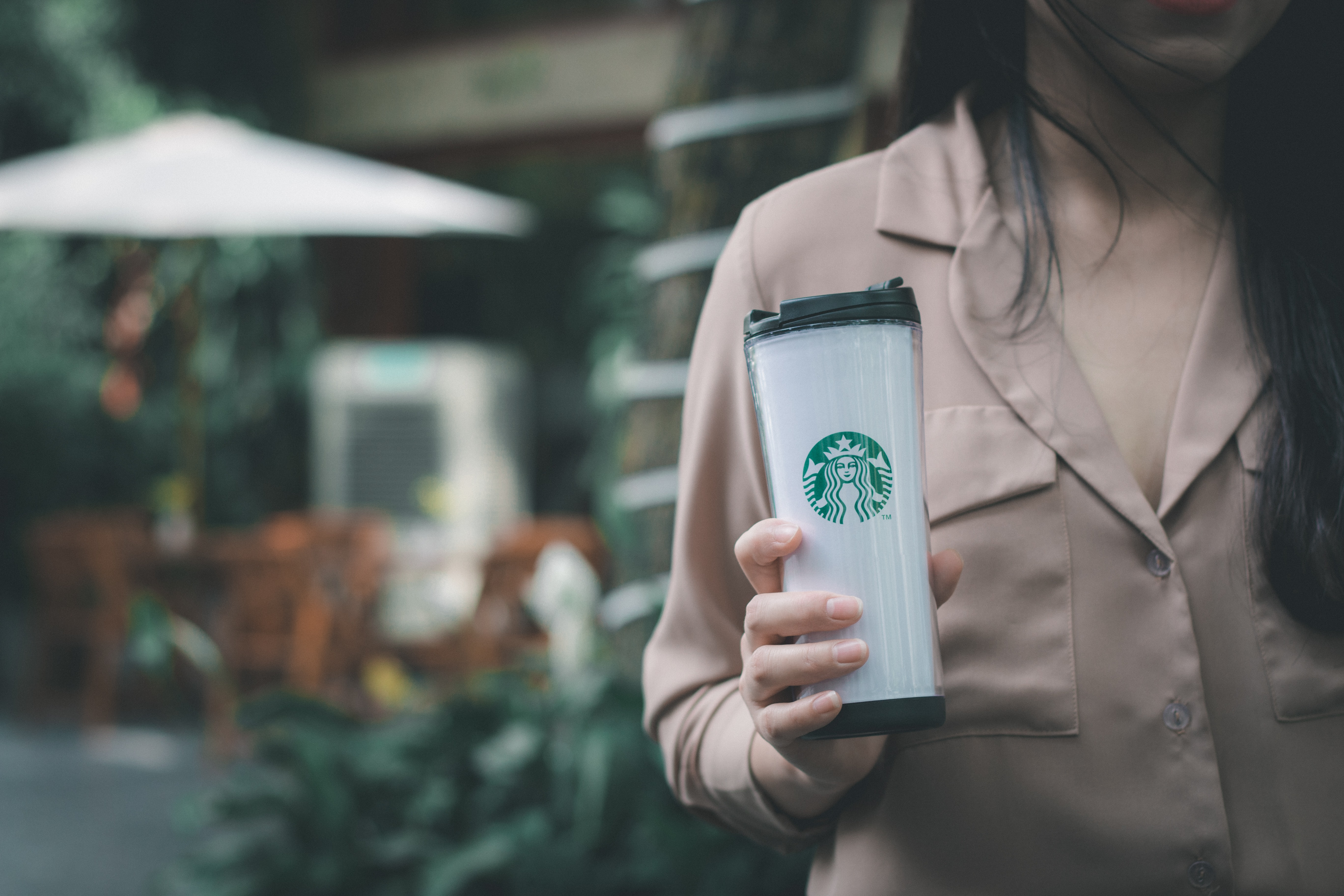 selective focus photo of woman holding Starbucks tumbler