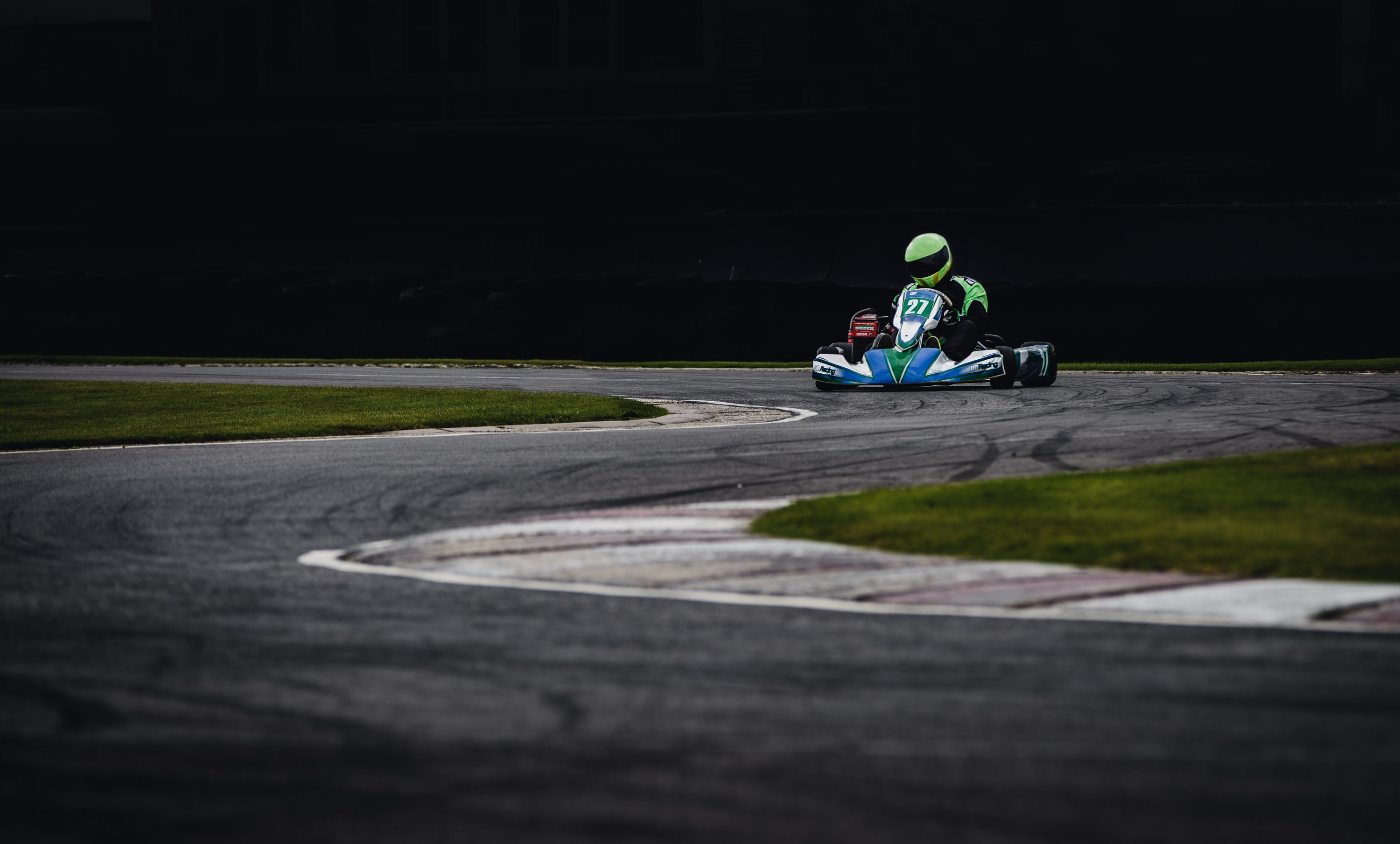 person riding go kart racing on race track