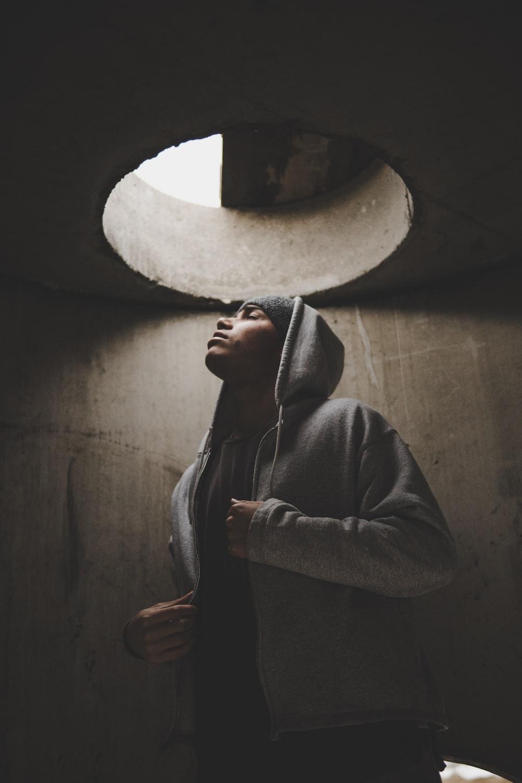 man wearing hoodie standing under manhole