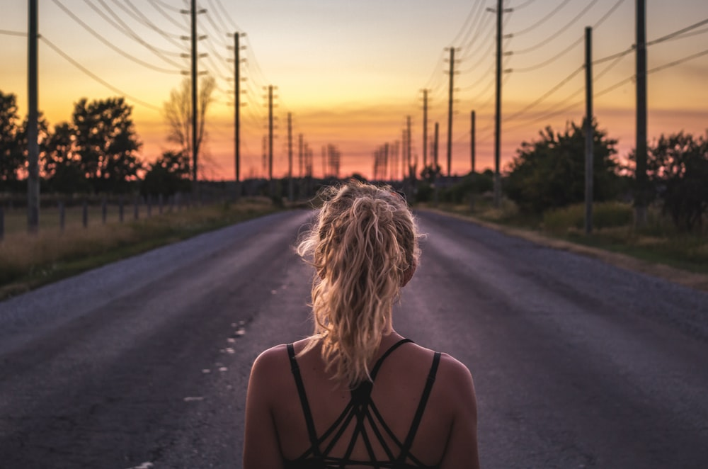 woman in black top walking on grey asphalt road during sunset