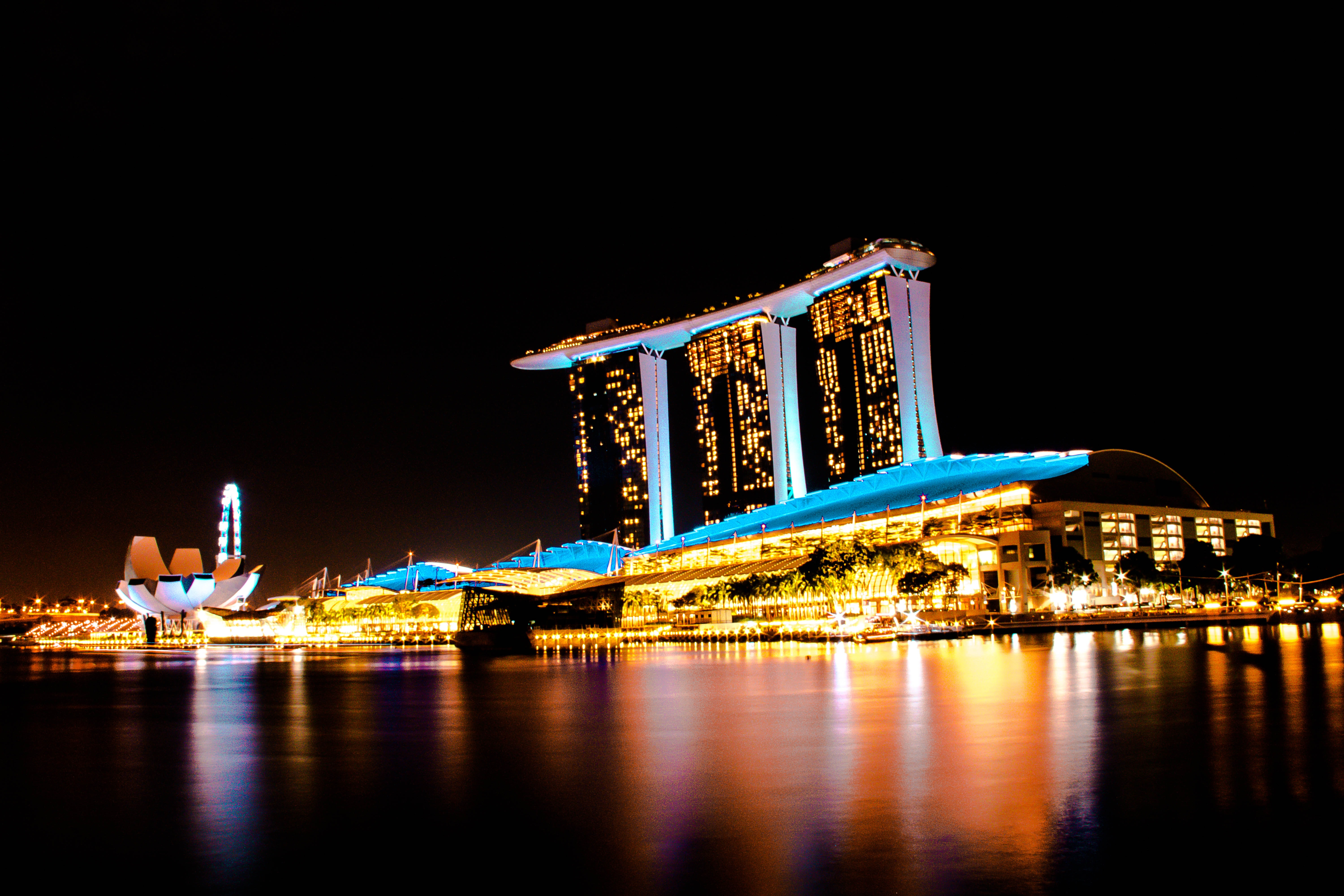 blue and yellow building fully lighted and surrounded with body of water