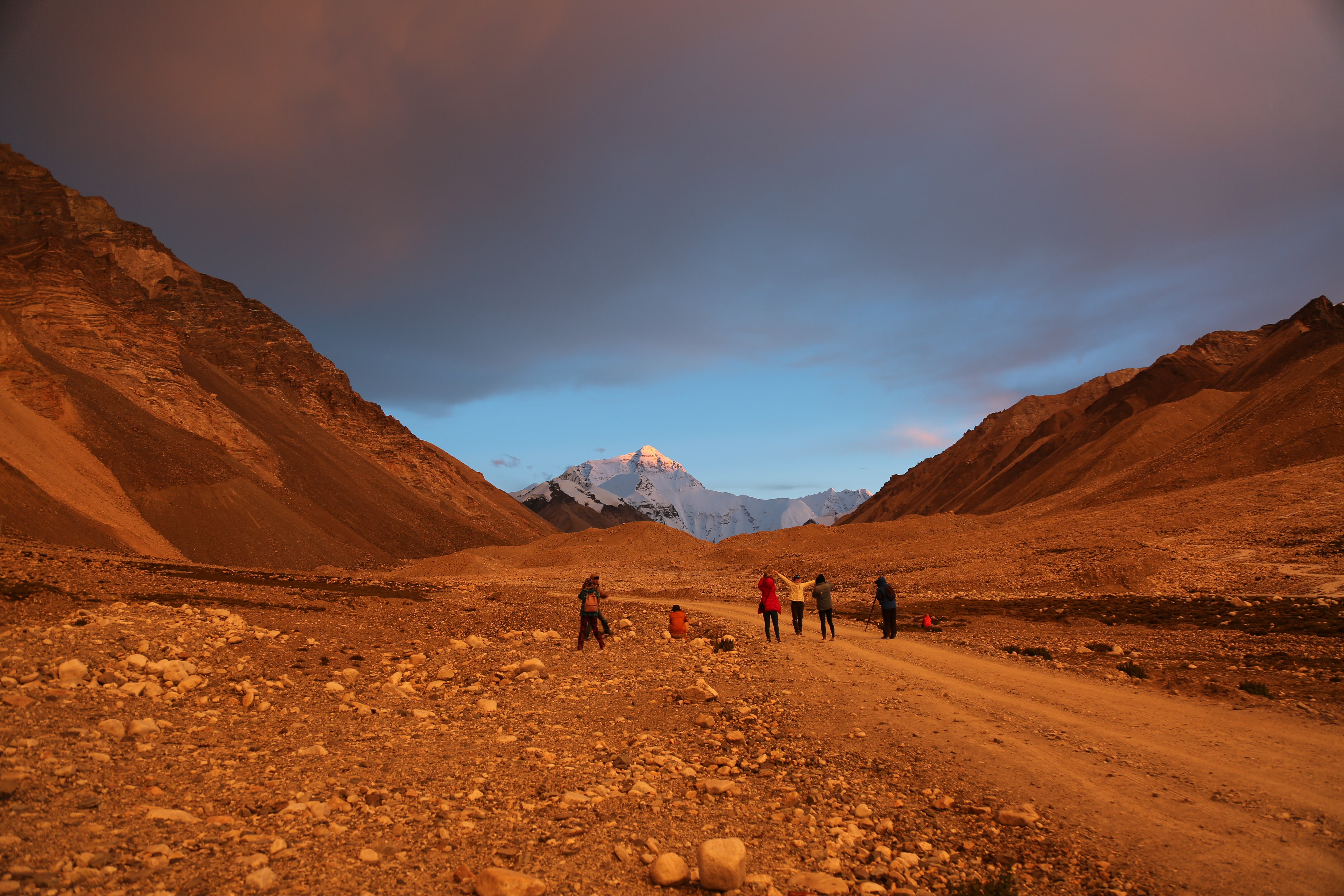 group of people walks on dirt road leading to mountain