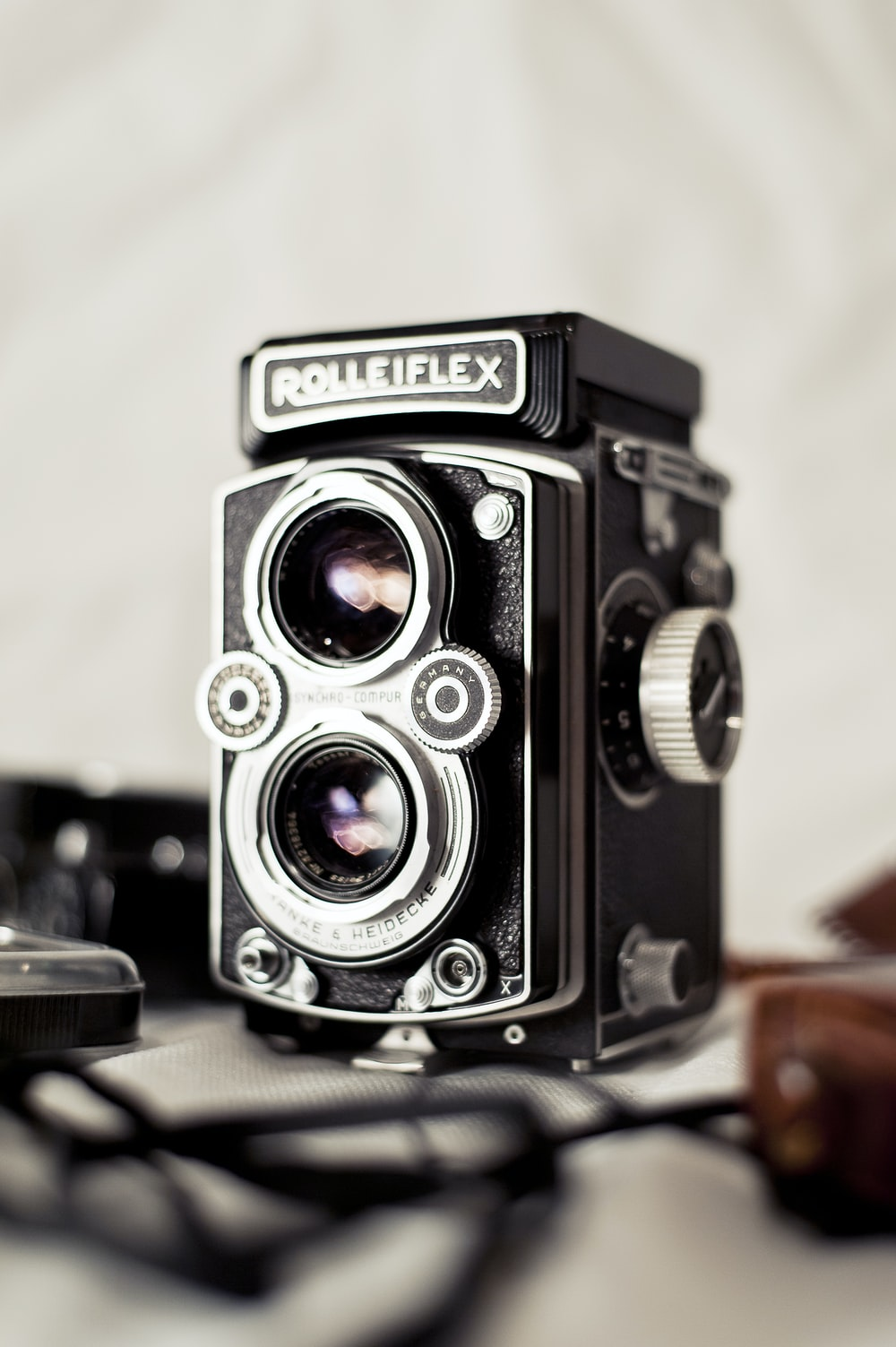 close view of black and gray Rolleiflex camera on gray surfaec