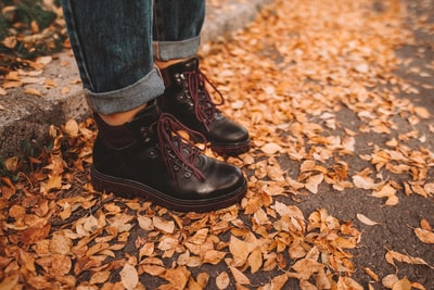 person wearing black leather work boots boot zoom background