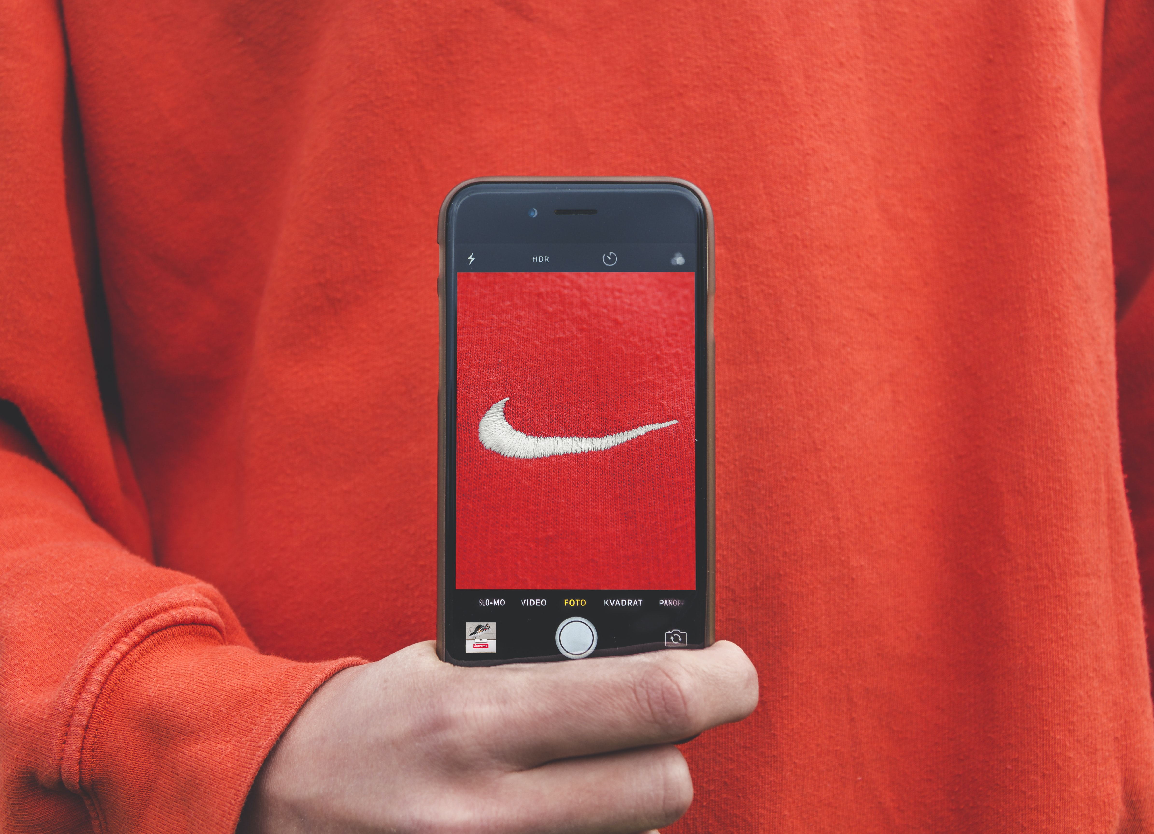 person holding iPhone taking picture on Nike label