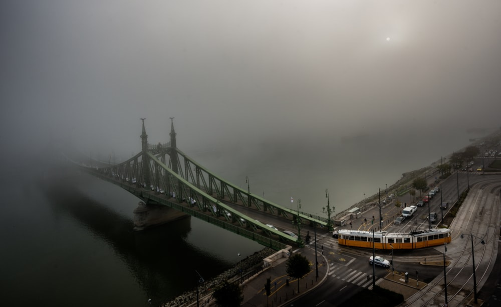 train towards gray concrete bridge covered by white clouds