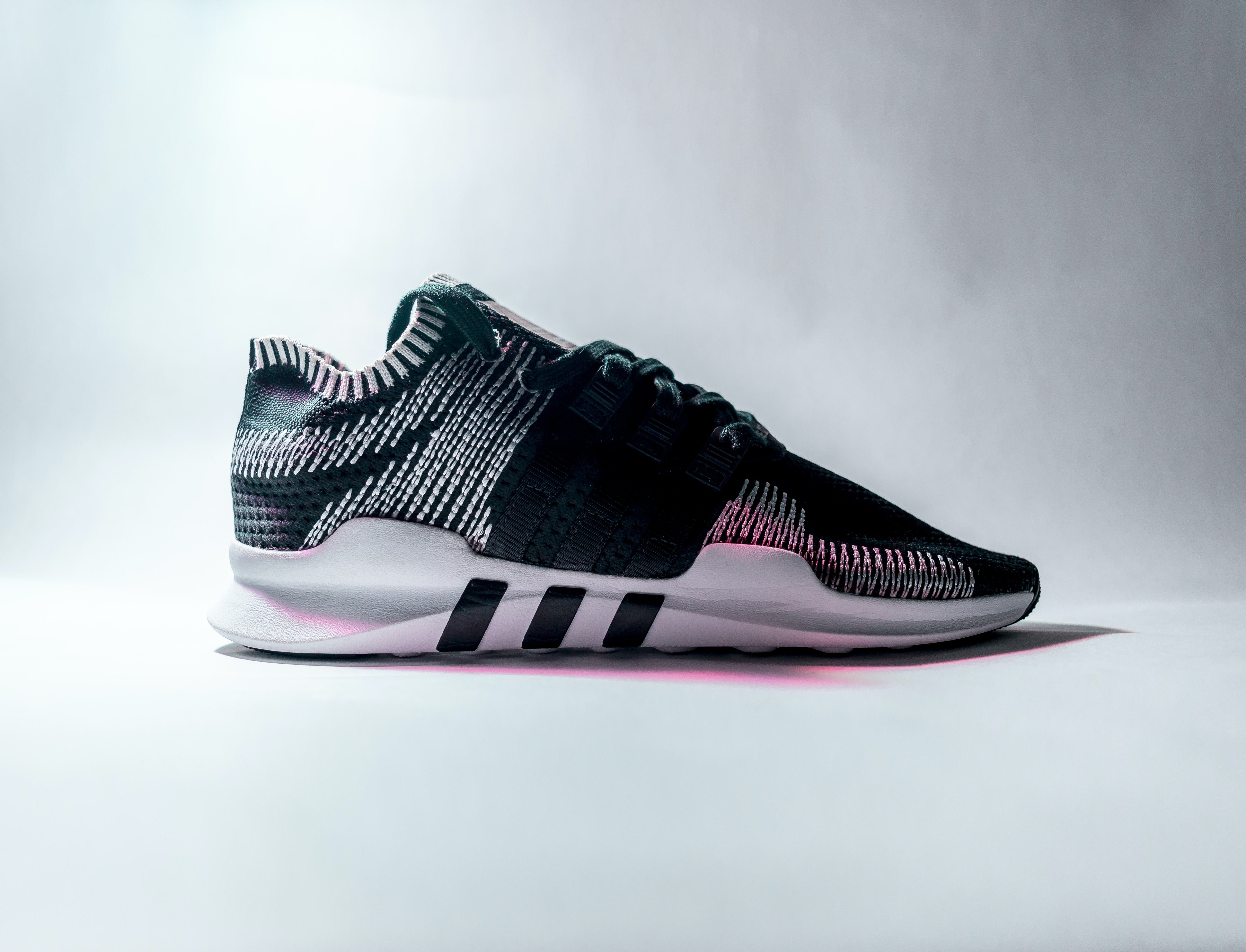 unpaired black and white Adidas low-top sneaker