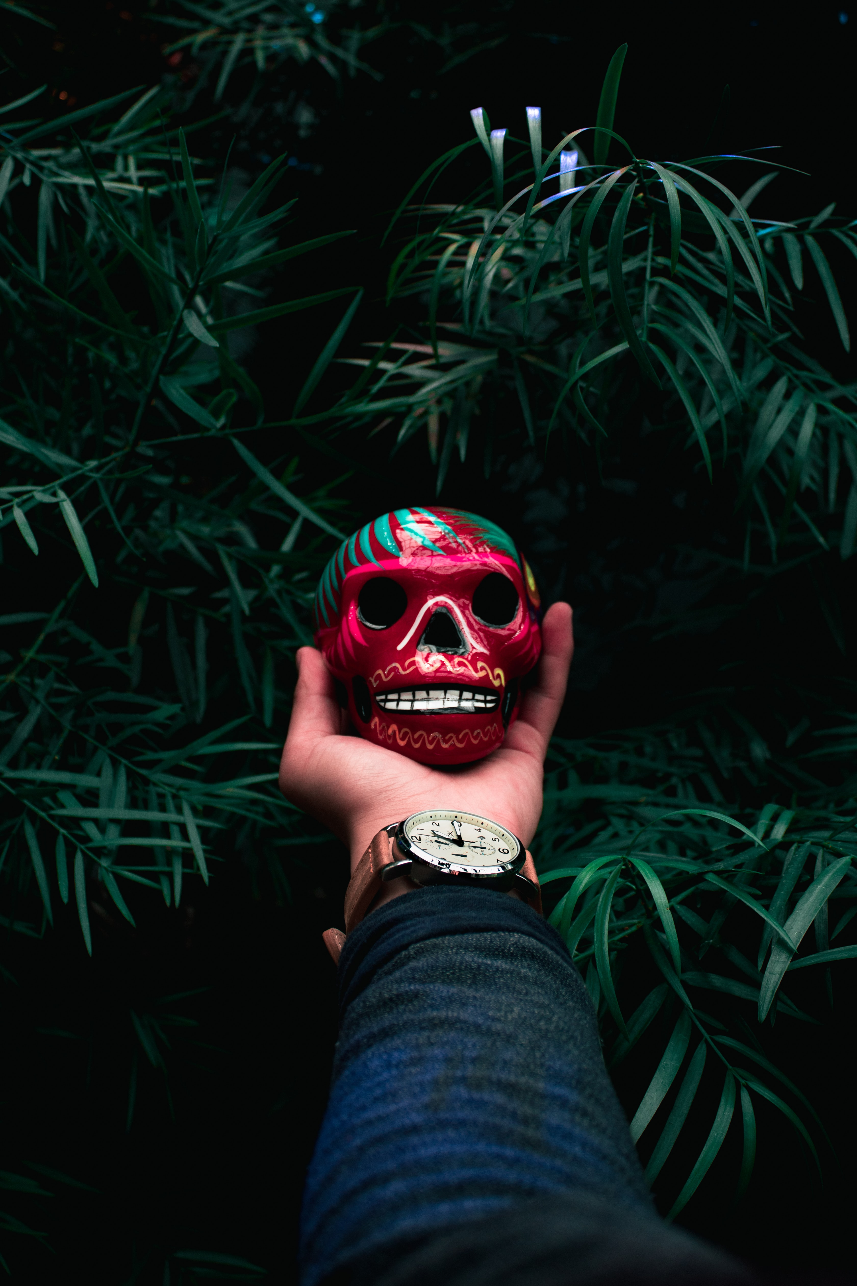 person holding red and green skull bauble