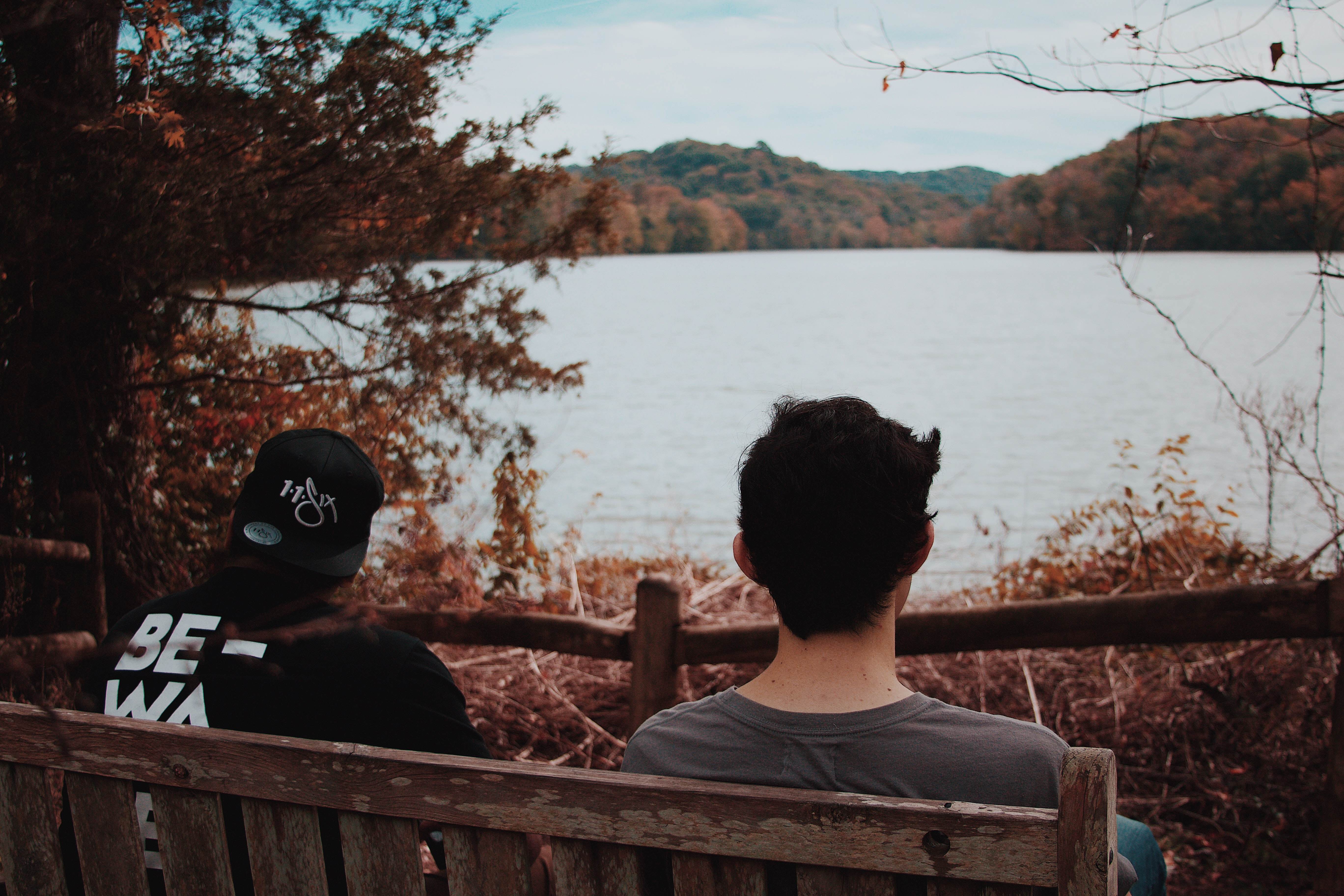 two men sitting on wooden bench looking at body of water
