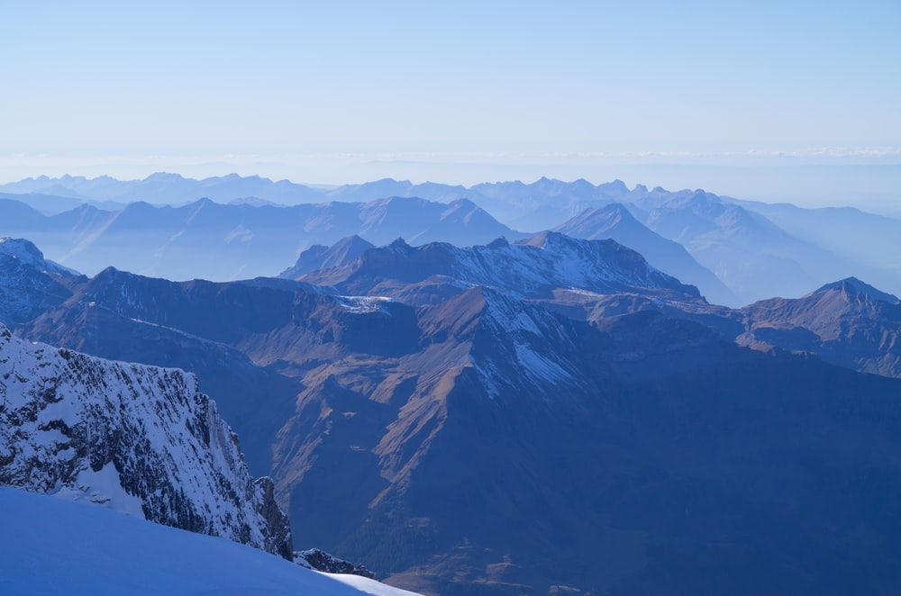aerial photography of mountains under blue and white sky