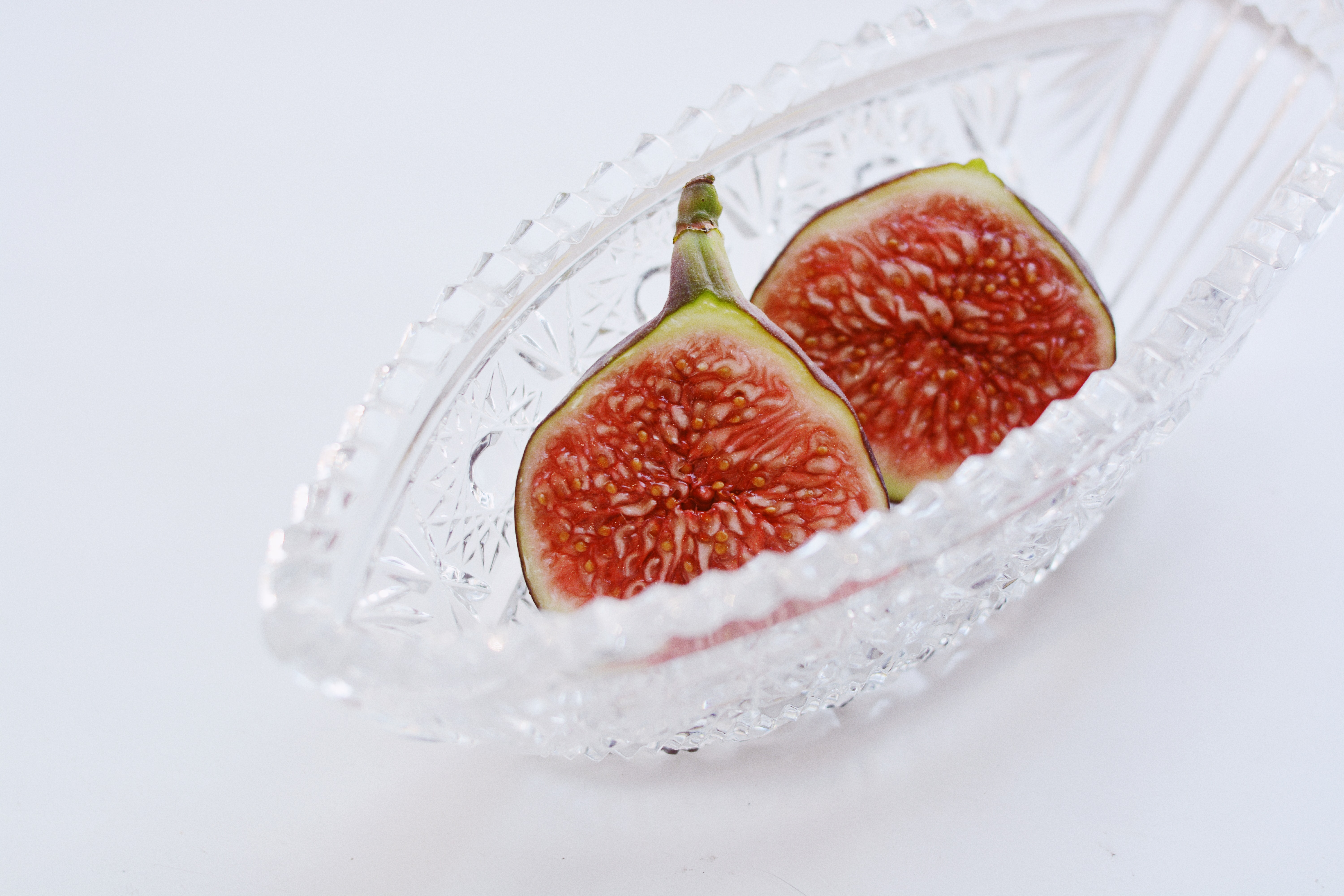 sliced red fruit in clear glass bowl