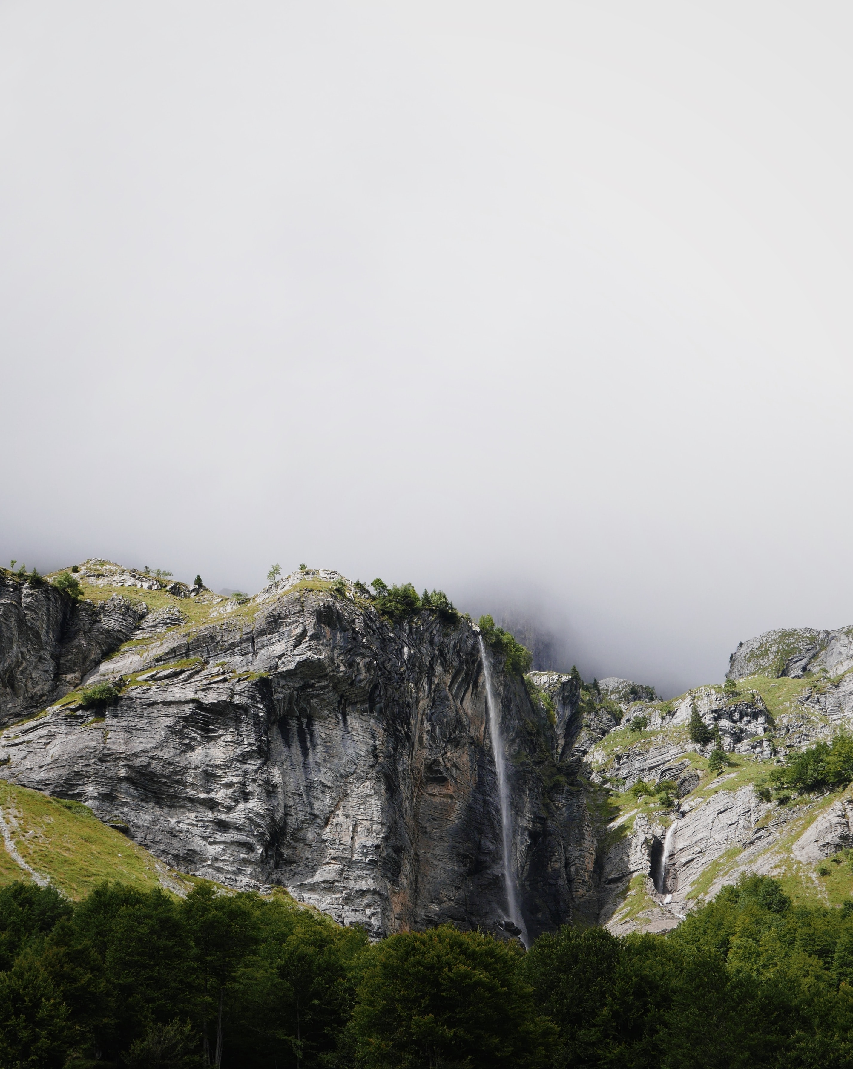 mountains covered with green trees under cloudy sky during daytime