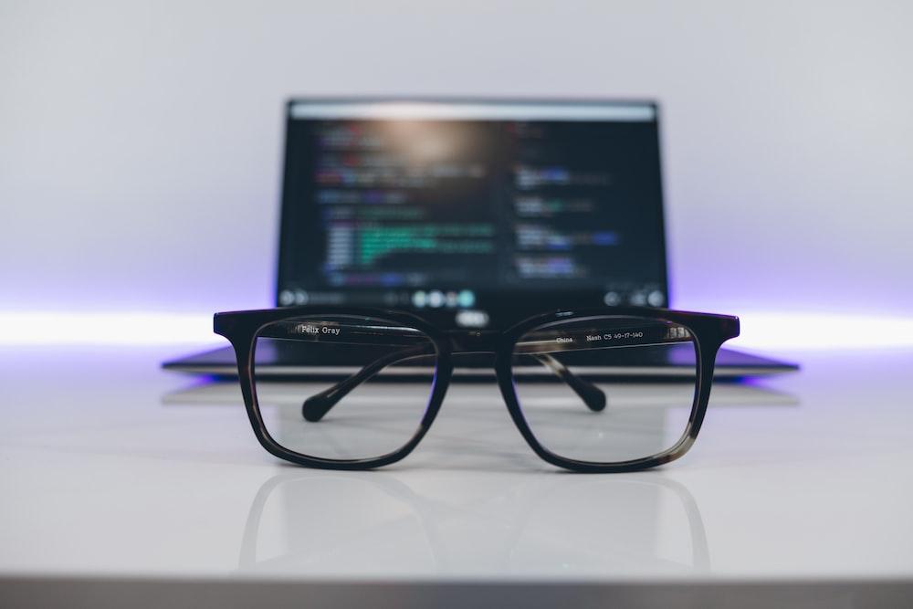 eyeglasses with black frames on white desk