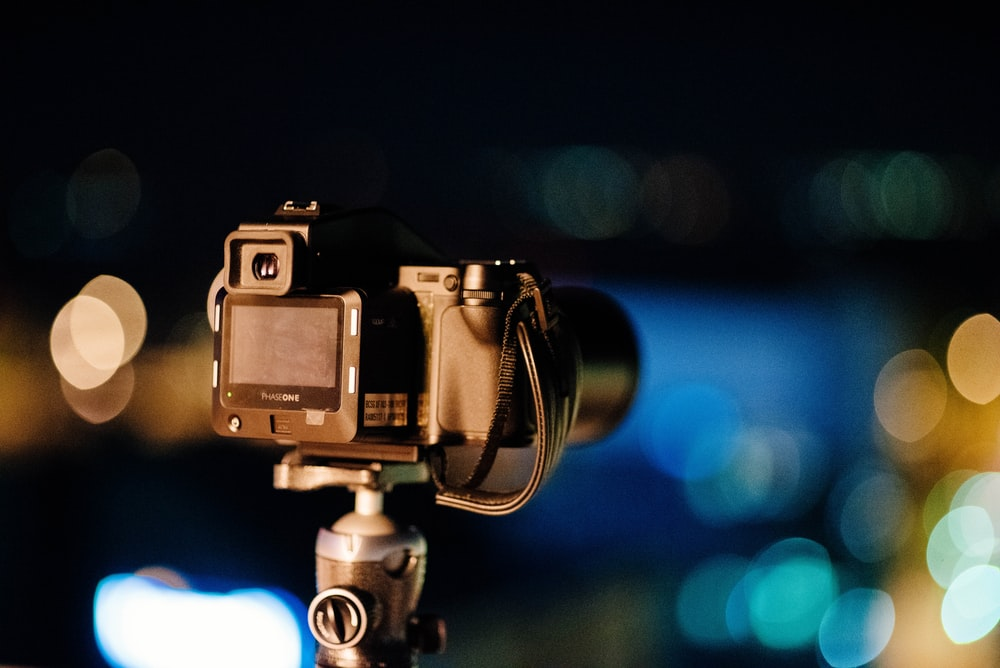 selective focus photography of black DSLR camera with stand