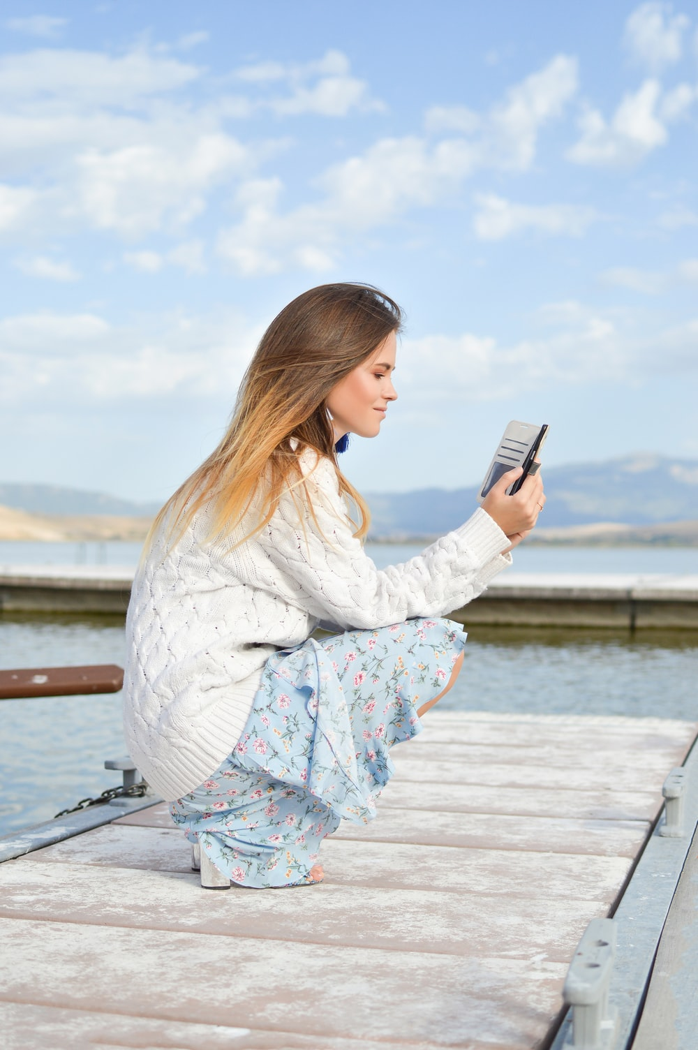 woman using smartphone while sitting of dock during daytime