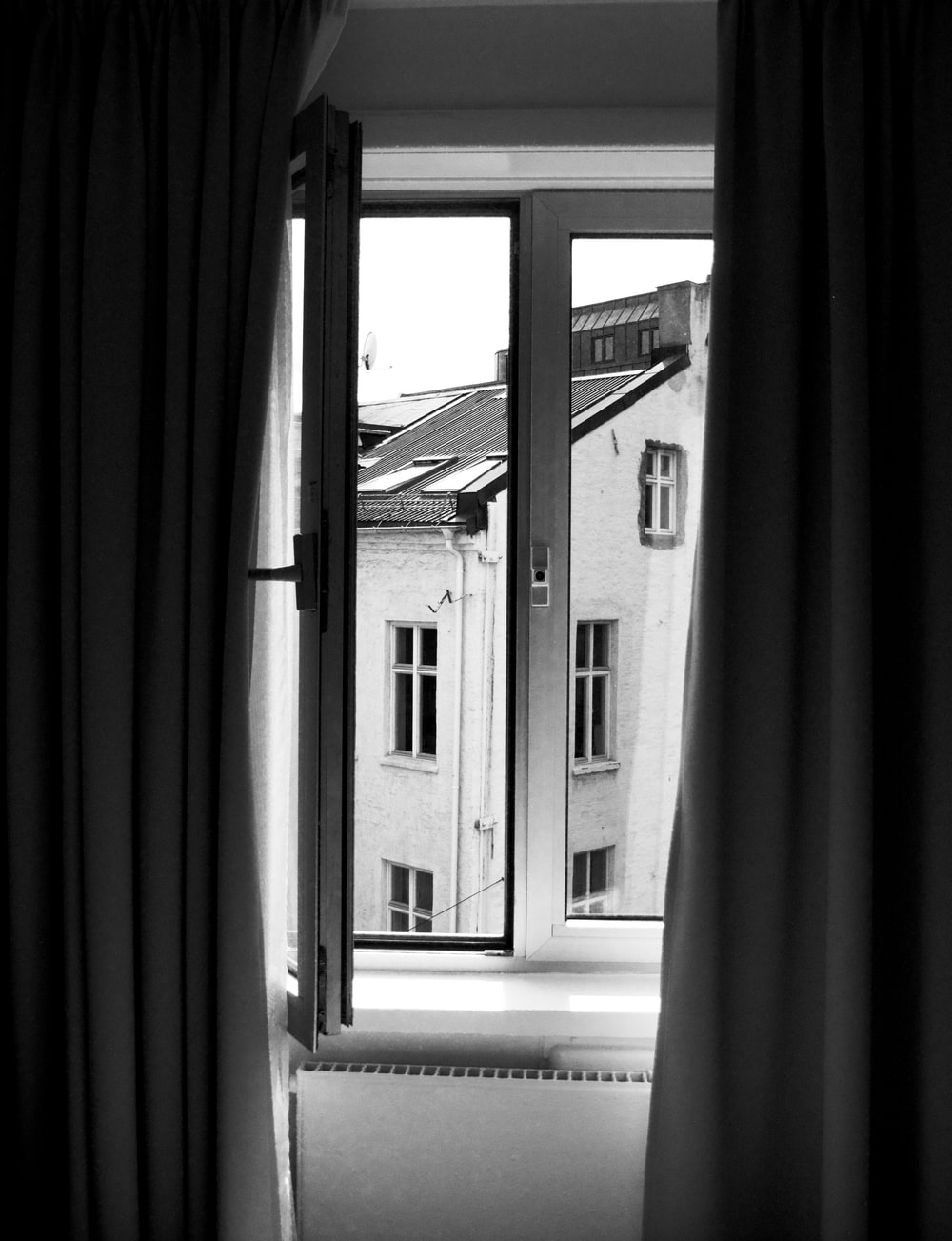 grayscale photo of wooden framed glass pane window opened