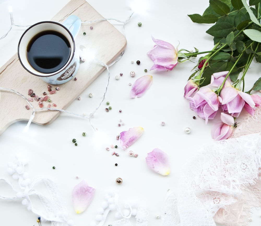 white ceramic mug filled with black liquid on beige chopping board beside pink roses on white surface