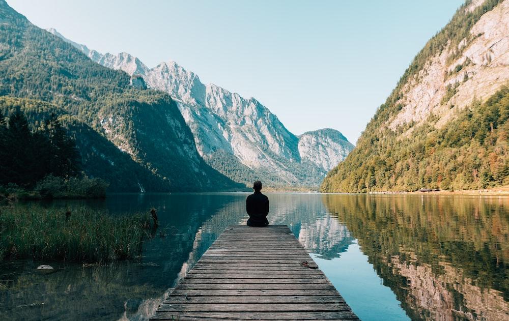 man sitting on gray dock