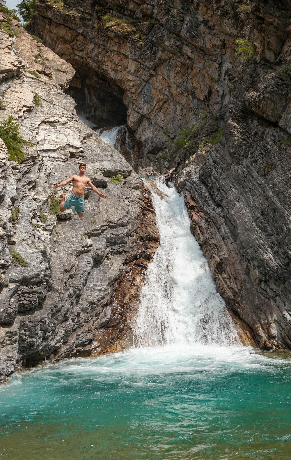 man jumping at body of water