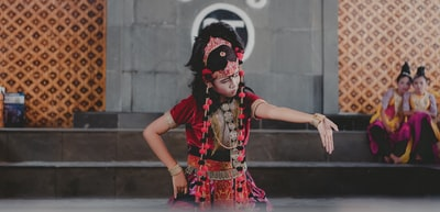 woman wearing red and black floral top dancing with two woman at her vicinity performance art teams background