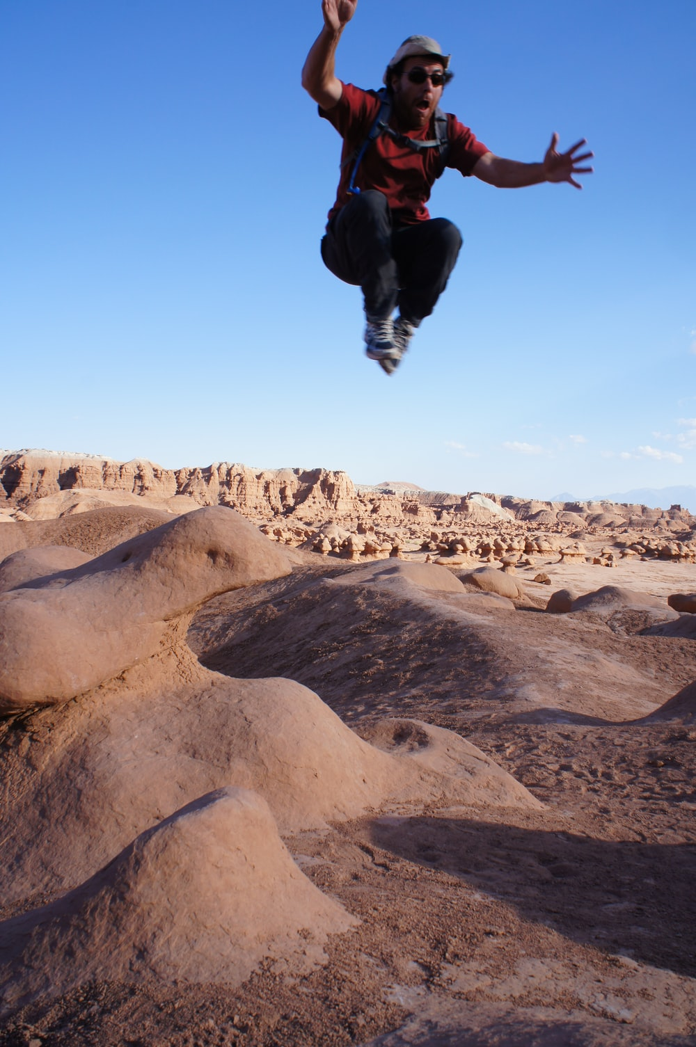 man jumped on desert during daytime