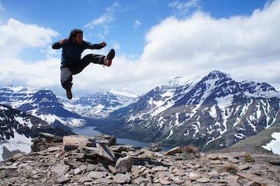 man jumping over gray stones glacier national park teams background