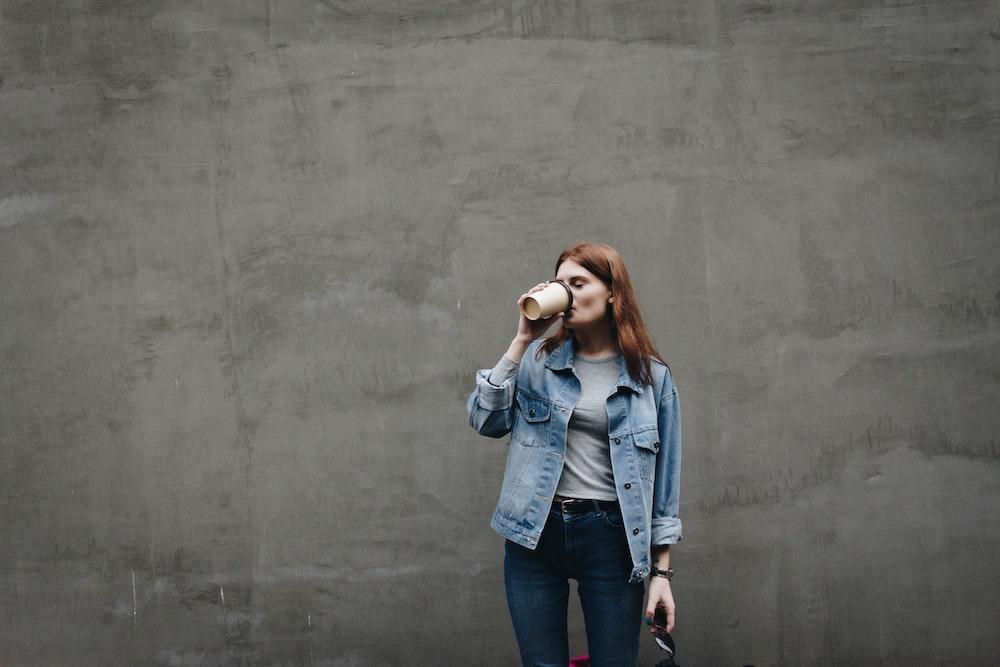 woman drinking on mug near gray wall during daytime