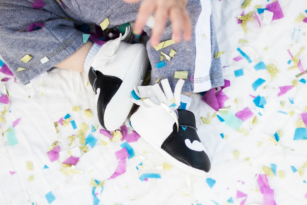 baby wearing white-and-black leather shoes
