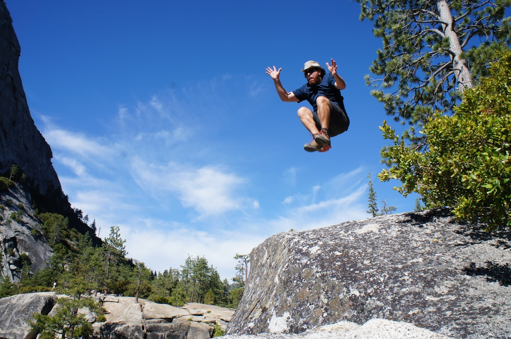 man jumping of rock formation near green tree at daytime