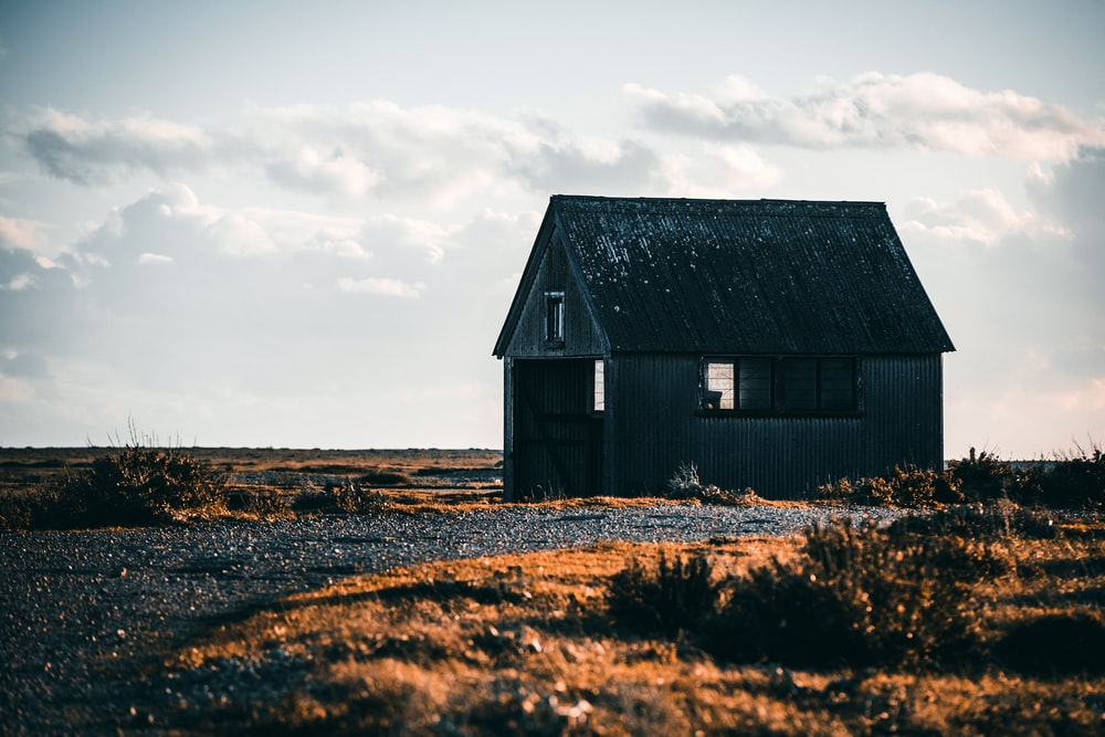 white hut on deserted land under white clouds during daytime