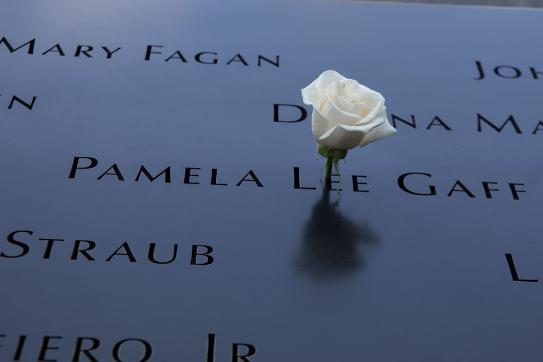 I visited Ground Zero Memorial. This shot is of the the plaque in memory of the fallen heros. Friends and family have placed this white rose in remembrance of their loved ones