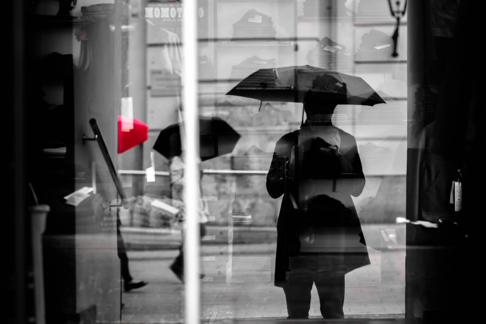 selectrive color photography of person with umbrellas