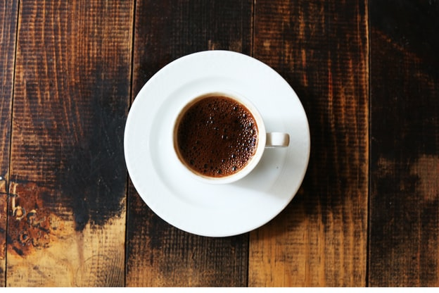 a full cup of black coffee sits on a wooden table