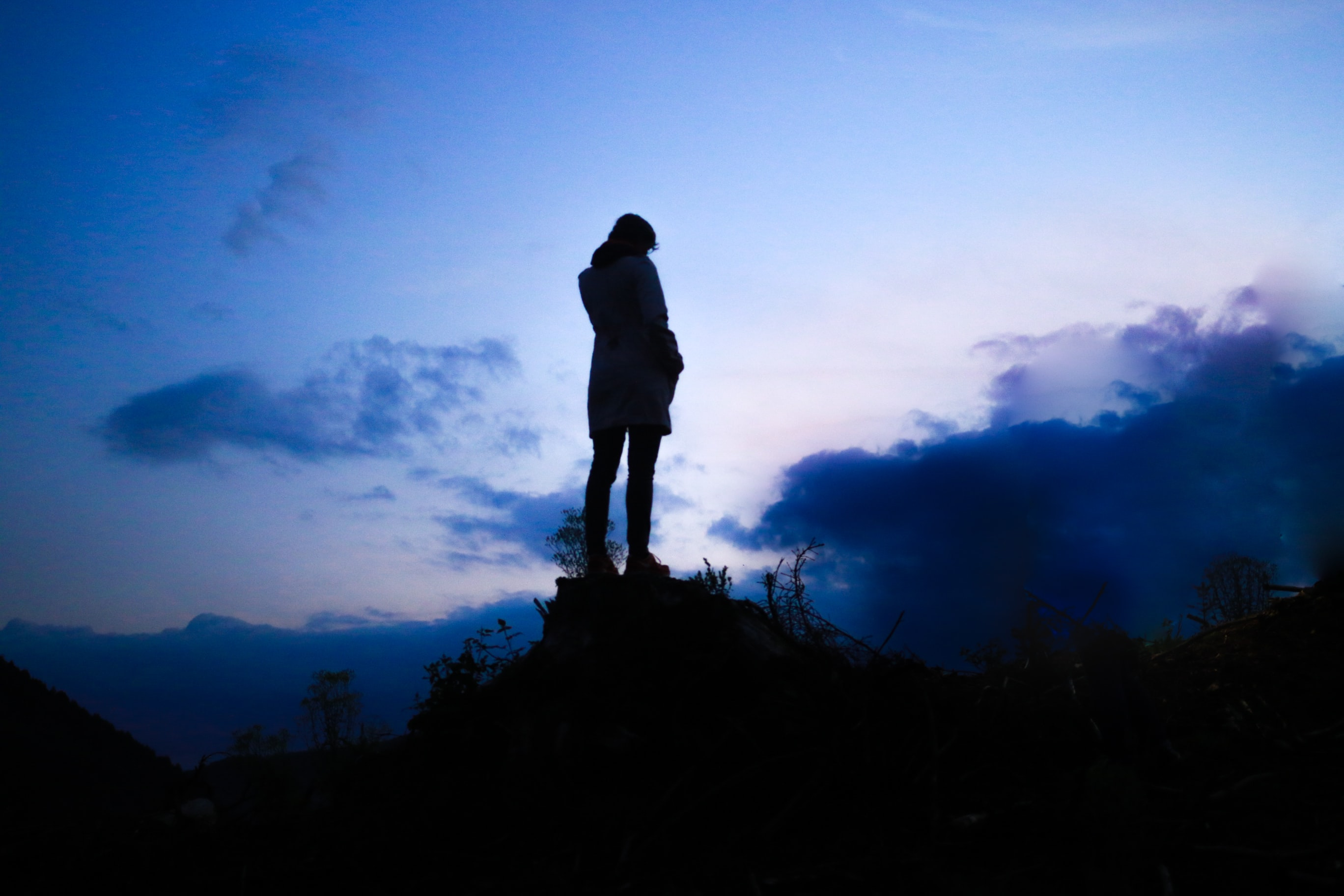person standing on boulder during twilight