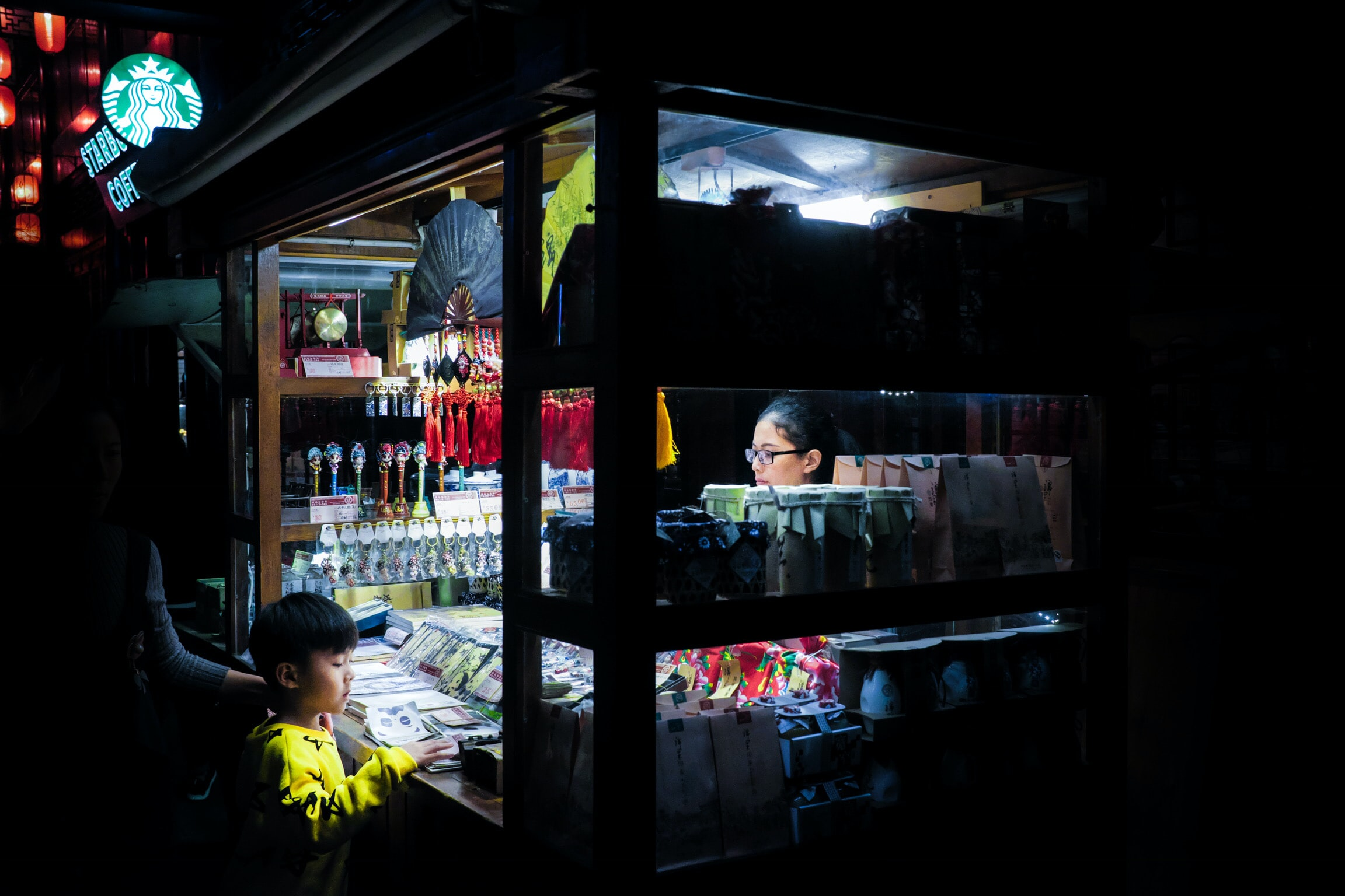 woman and boy in food stall at night time