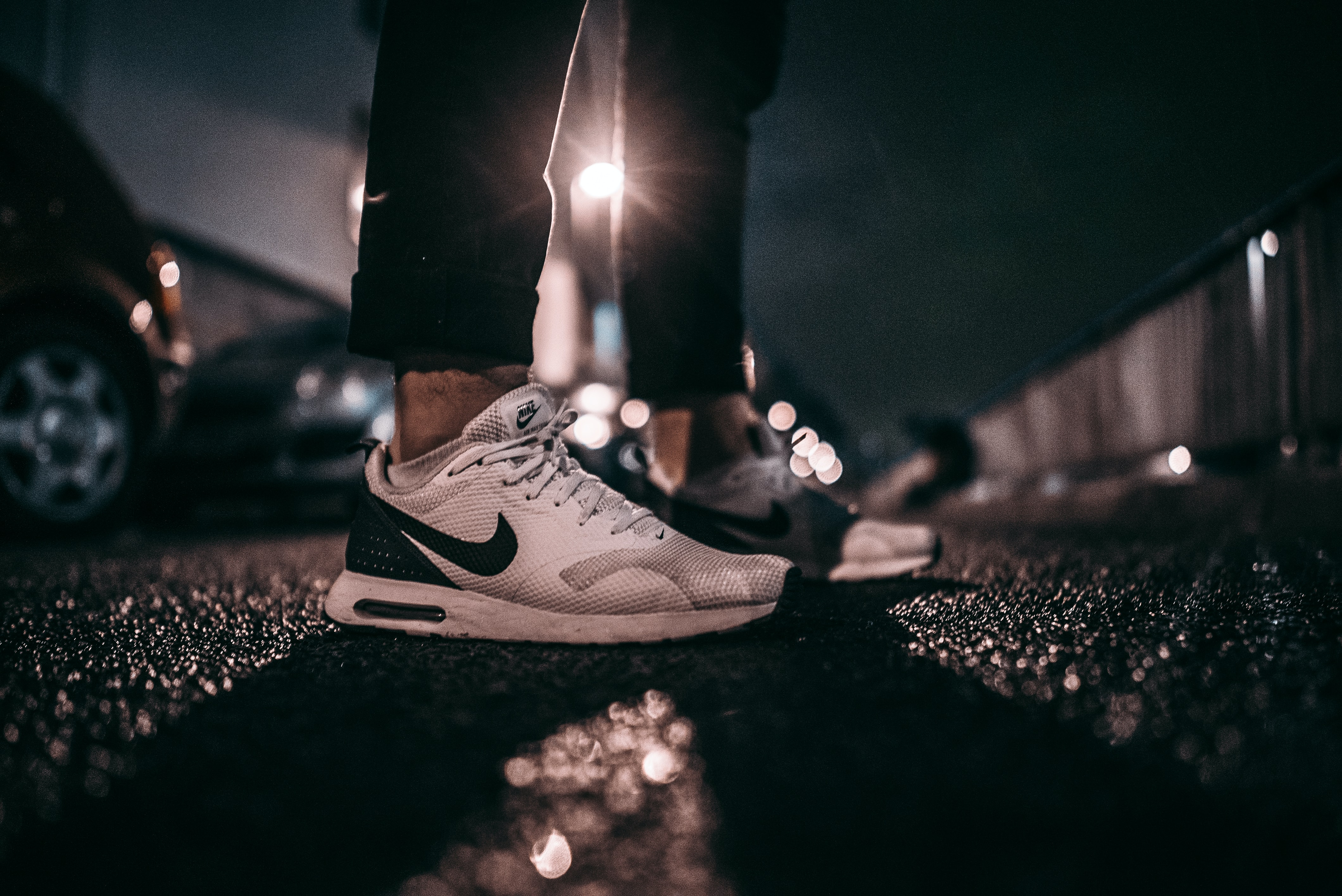 person wearing white and black Nike shoes