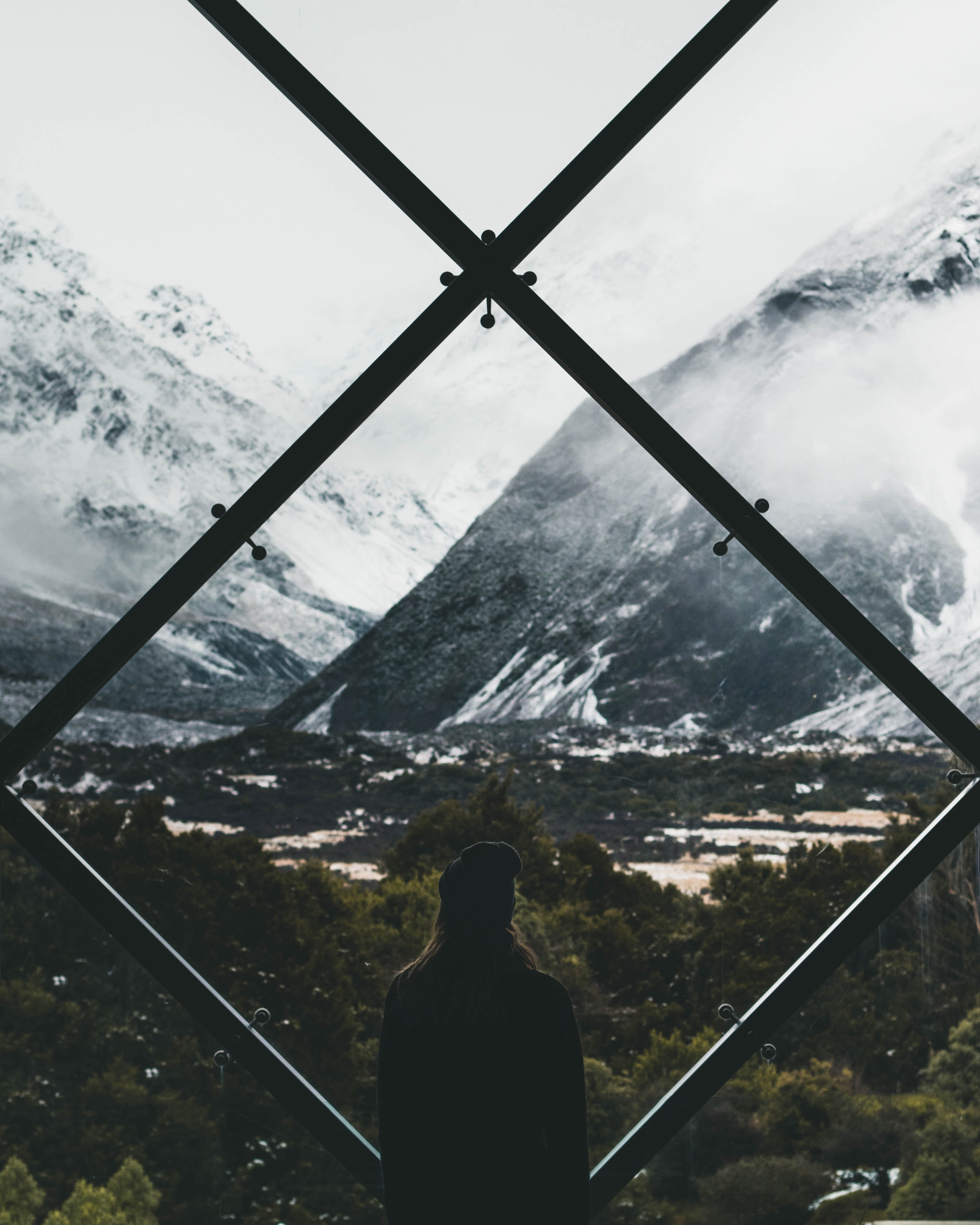 person standing on stained window looking through snow covered mountain