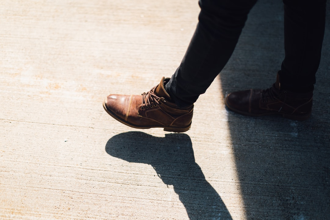 person wearing brown leather boots walking on gray concrete during daytime