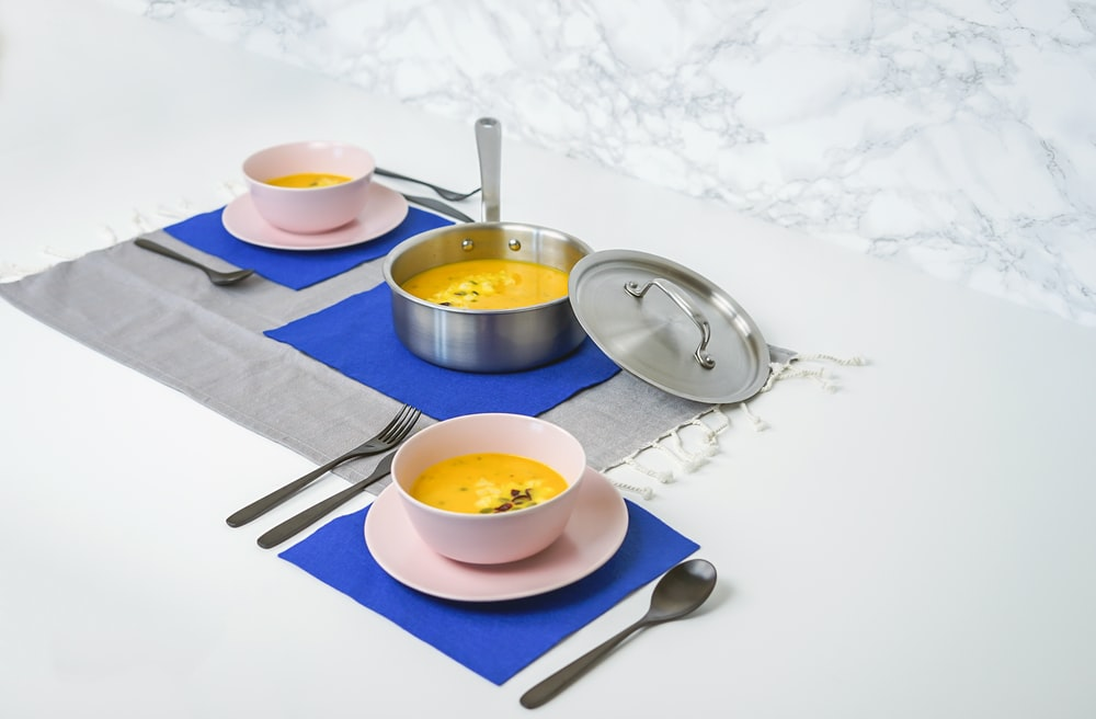 soup dish in pot and ceramic bowl