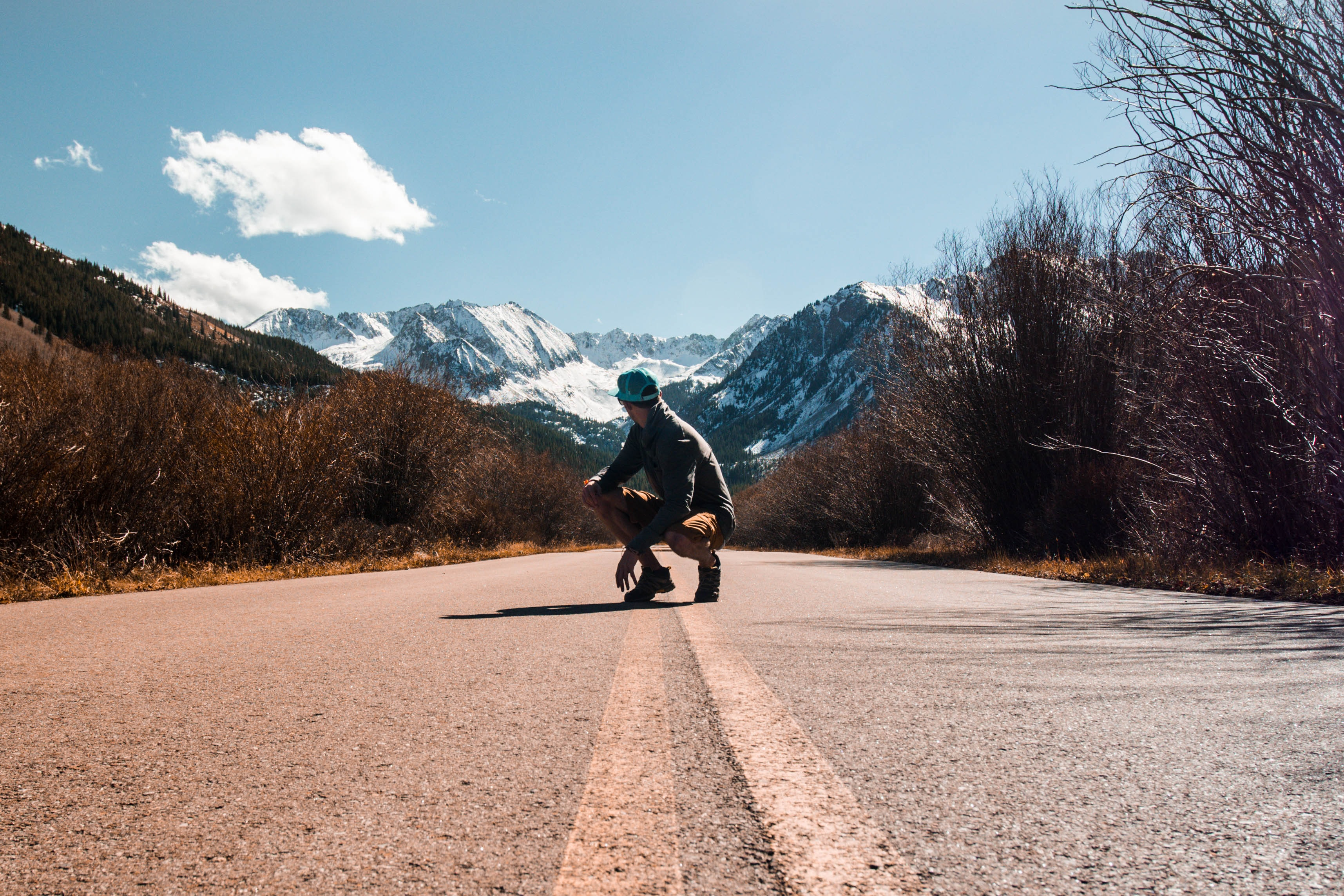 person squatting in the middle of road near snow-capped mountain at daytime