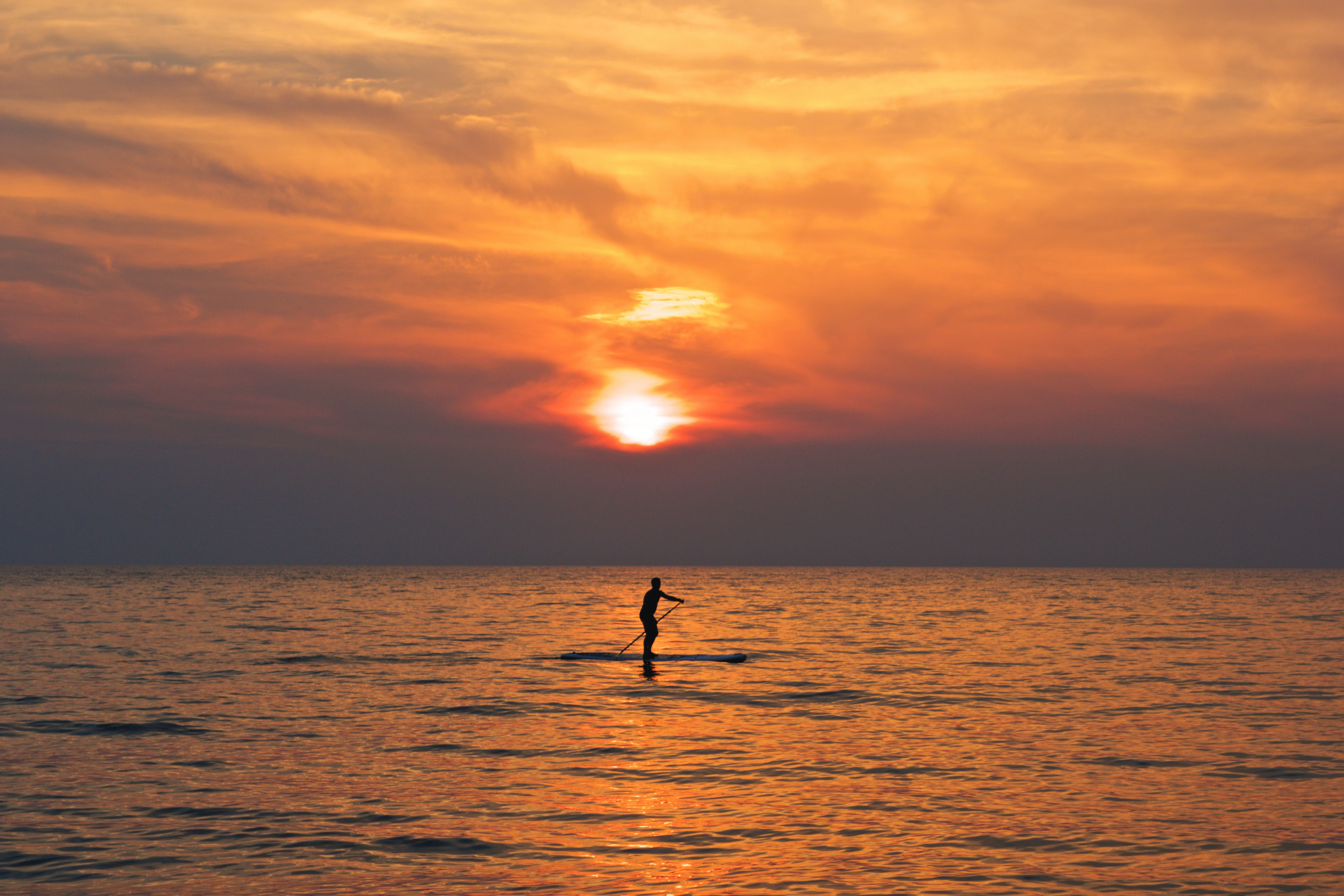 silhouette of person on boat holding paddle during golden hour