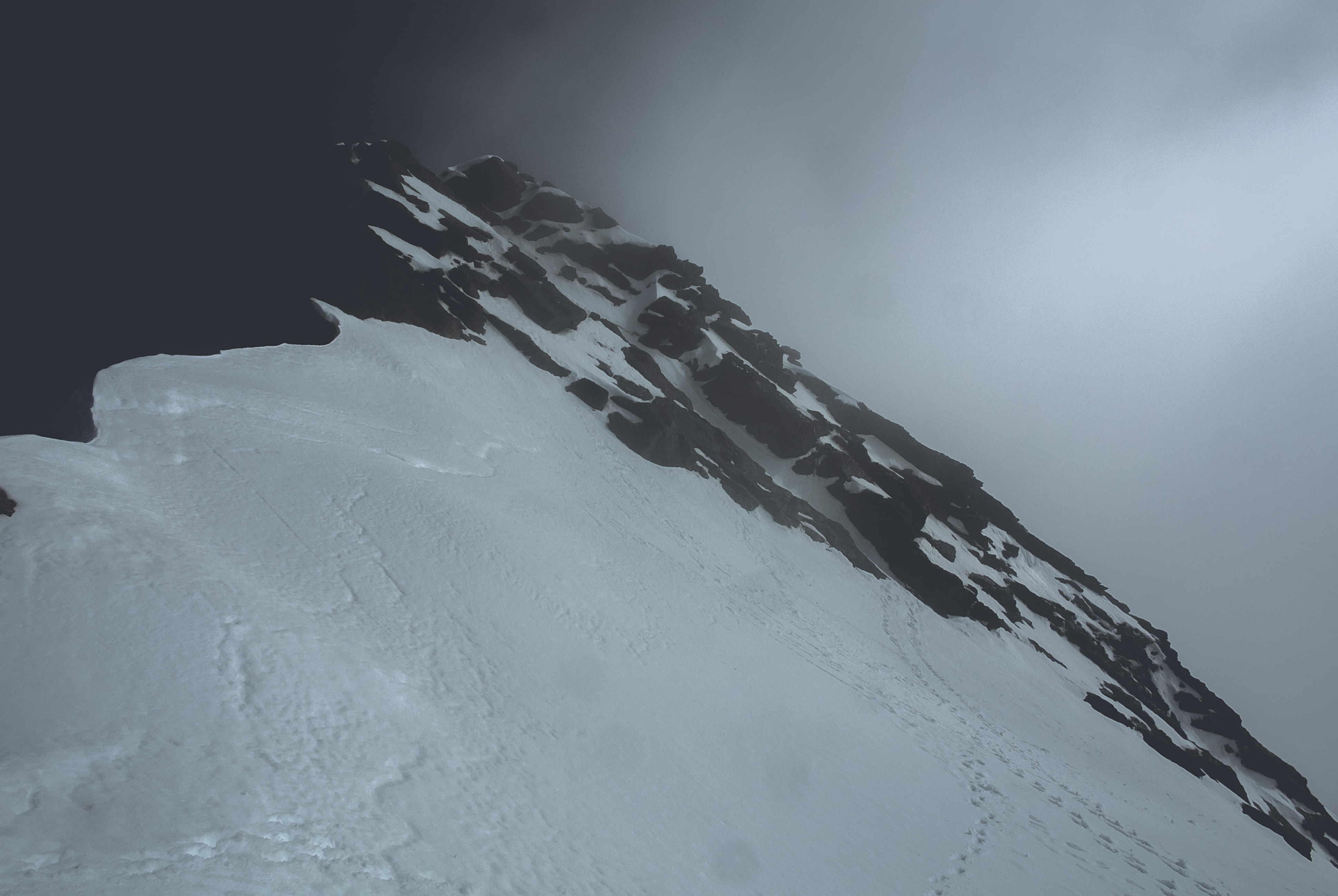 snow covered mountain under white clouds at daytime