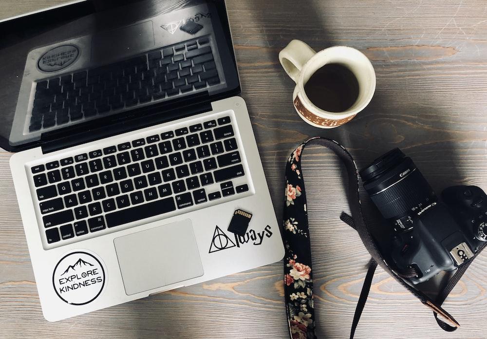 black and gray laptop computer beside black DSLR camera and white ceramic mug
