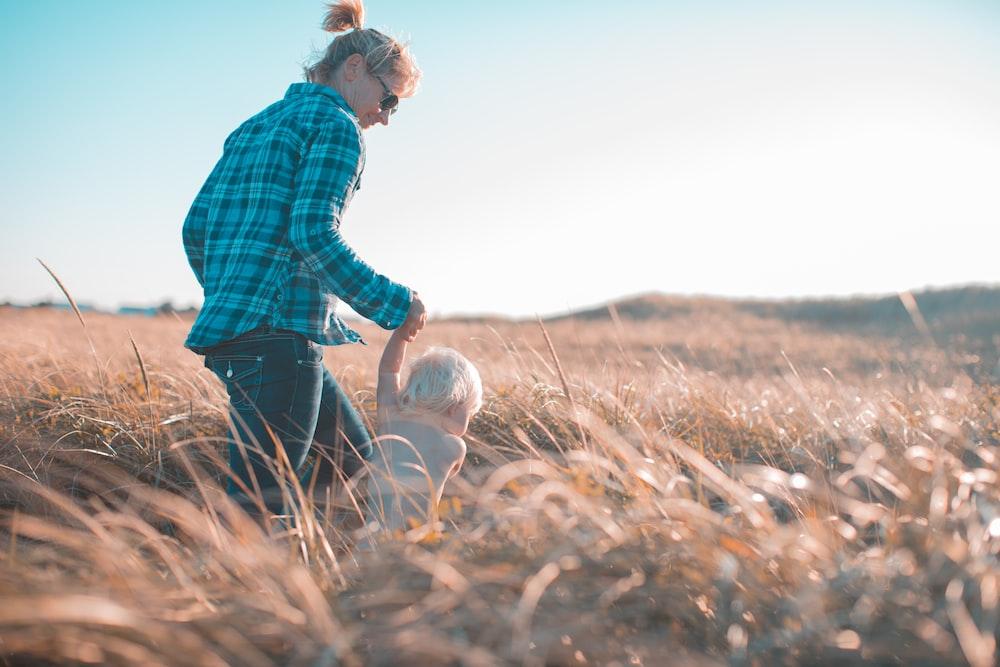 woman holding toddler waling near brown grass during daytime