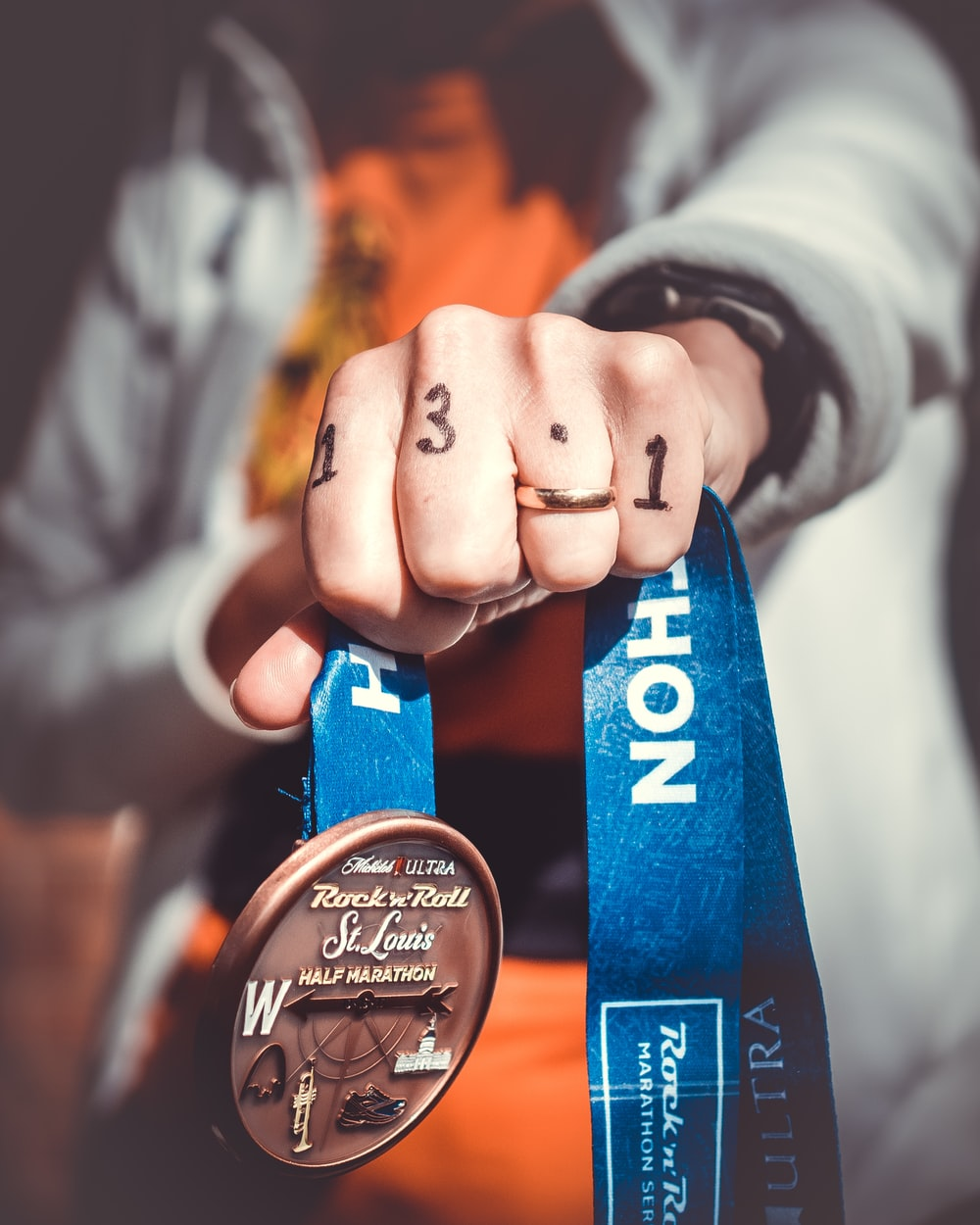 person holding Rock N Roll St. Louis half marathon medal
