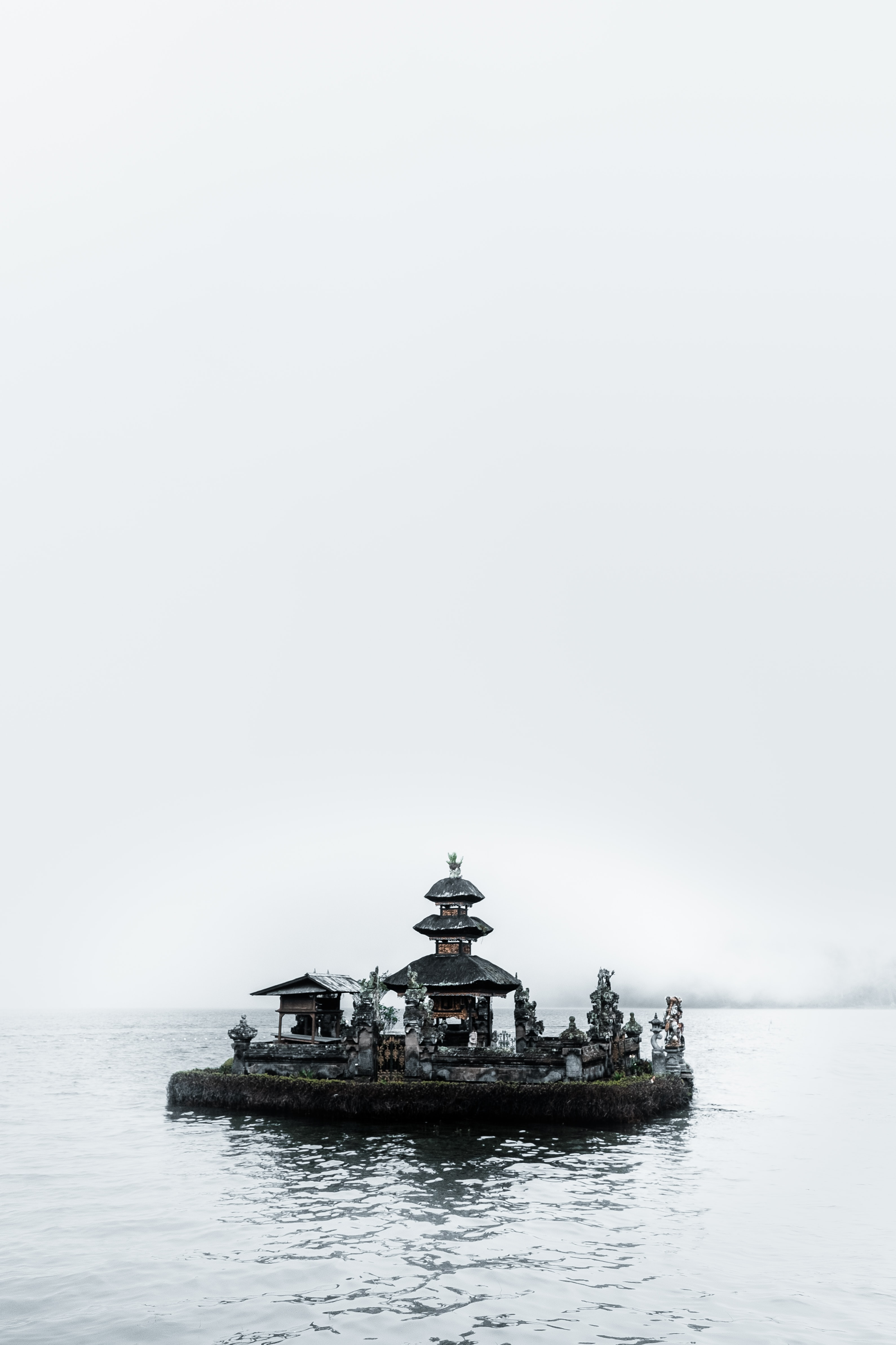 black and brown temple surrounded sea under gray sky