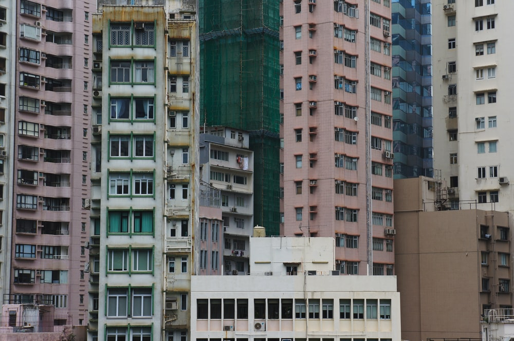 white painted building near pink high-rise building
