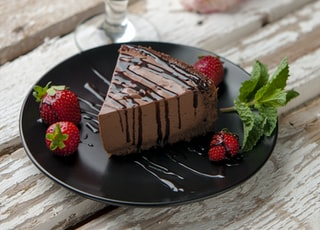 chocolate cake beside strawberries and wine glass