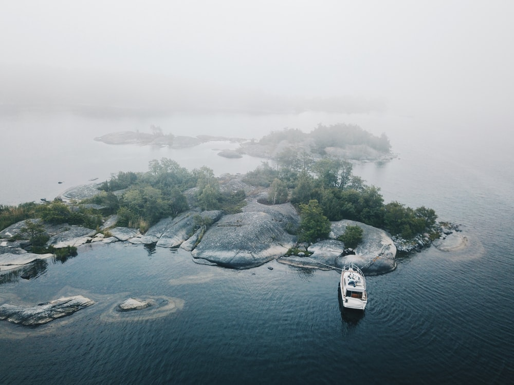 aerial photo of white yacht dock beside gray and green island with mist at daytime