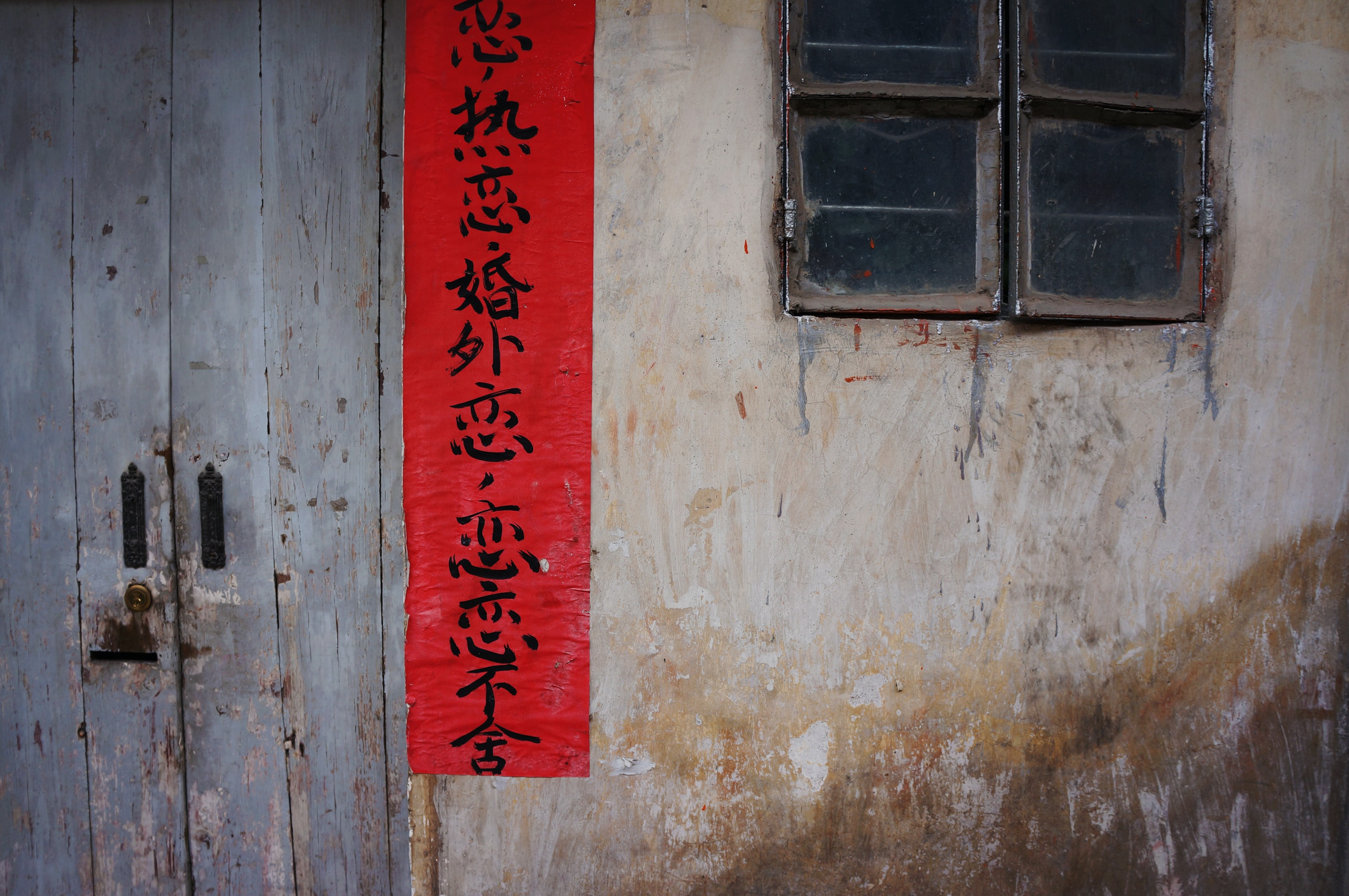 red signage near gray wooden door